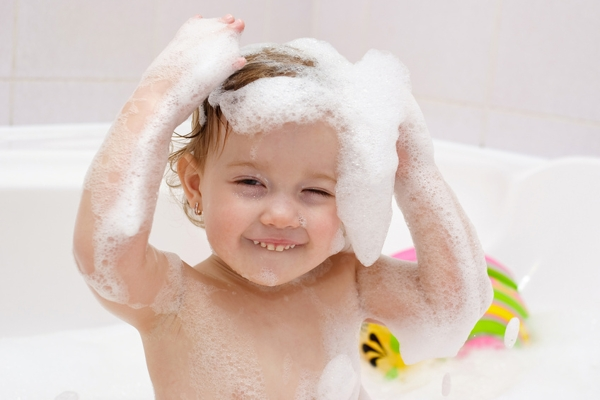 cute baby is washing her hair in bath